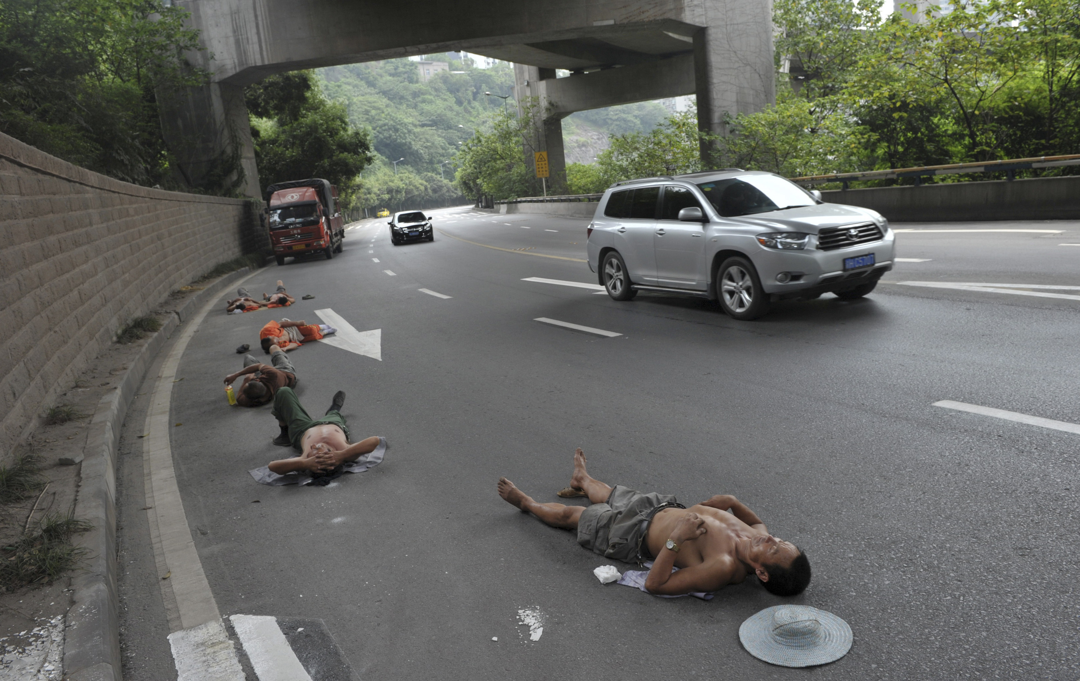 Labourers who work nearby nap on a road as cars drive past in Chongqing Municipality, July 23, 2013. Picture taken July 23, 2013. REUTERS/Stringer (CHINA - Tags: SOCIETY TPX IMAGES OF THE DAY) CHINA OUT. NO COMMERCIAL OR EDITORIAL SALES IN CHINA - RTX11WRT