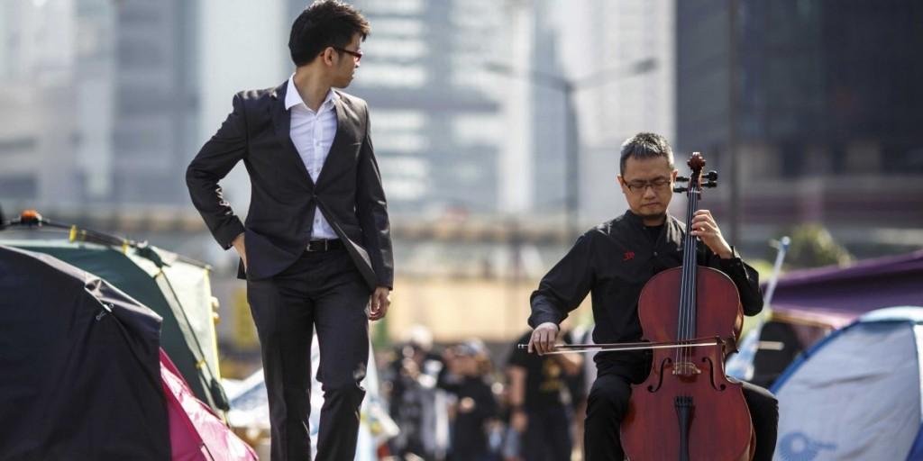 Виолончелист играет на мосту , заполненном палатками , созданными протестующими сторонниками демократии в финансовом центре Гонконга, 9 декабря 2014. Источник - Reuters