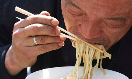 Китаец есть лапшу одноразовыми палочками