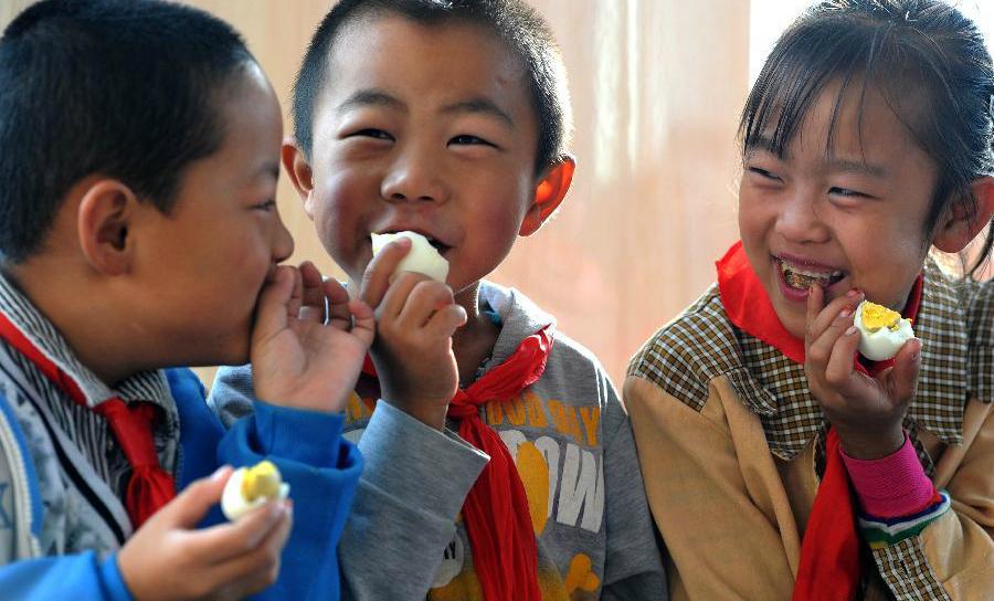 маленькие китайцы едят вареные яйца