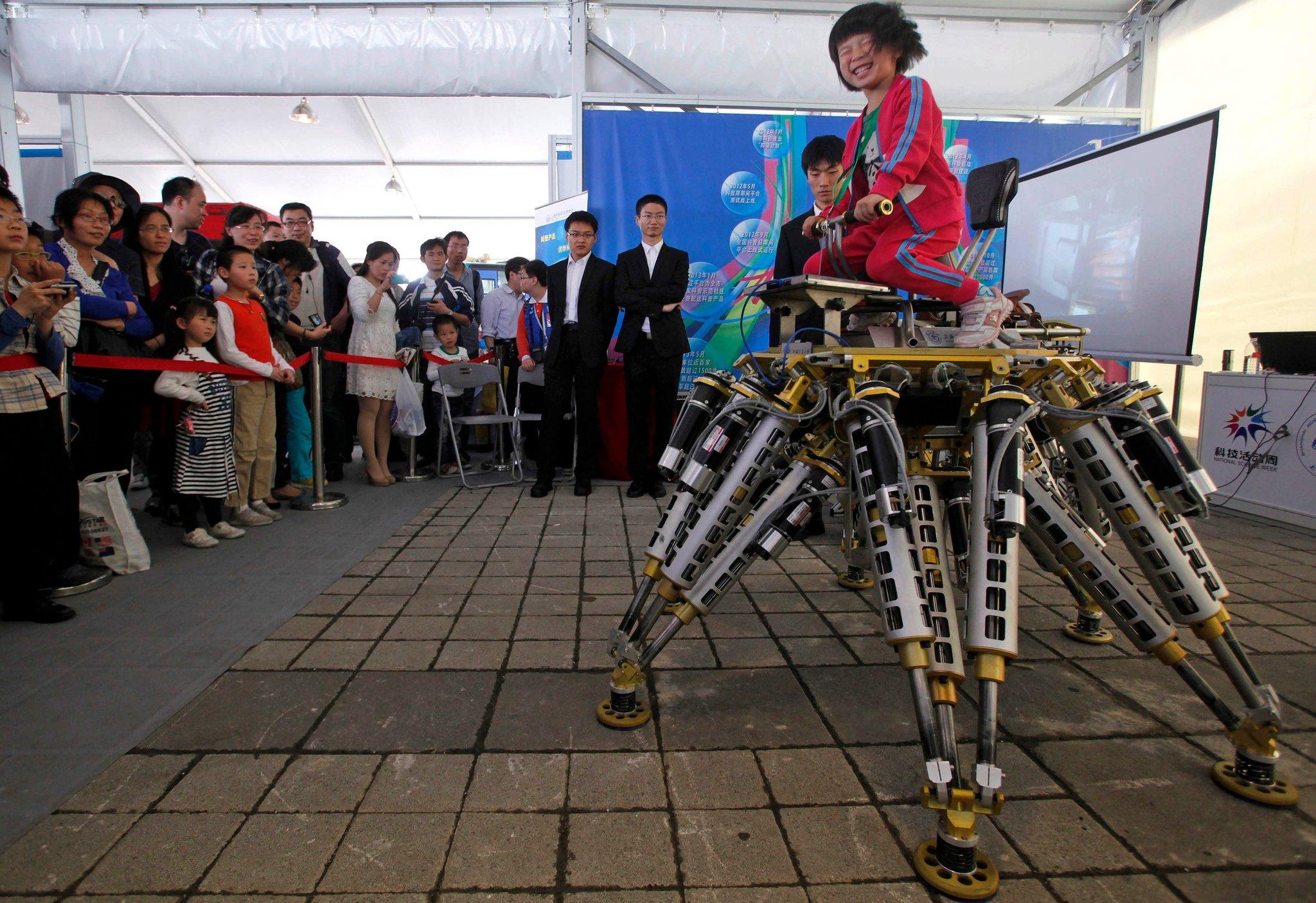 китайская девочка управляет роботом