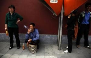 Китаец курит на остановке