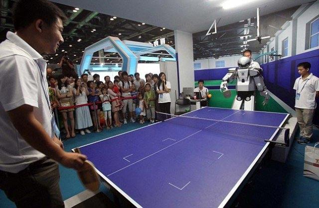 Человек играет в теннис с роботом