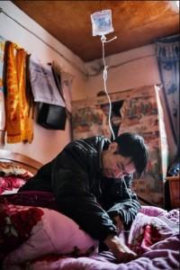 Хэ Цюаньгуй под капельницей в своей постели. Фото: Сим Чи Инь / VII