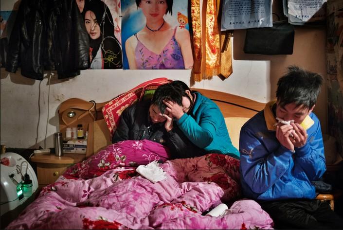 Хэ с женой и 18-летним сыном после очередной попытки суицида. В 2013 году он трижды пытался покончить с собой. Фото: Сим Чи Инь / VII