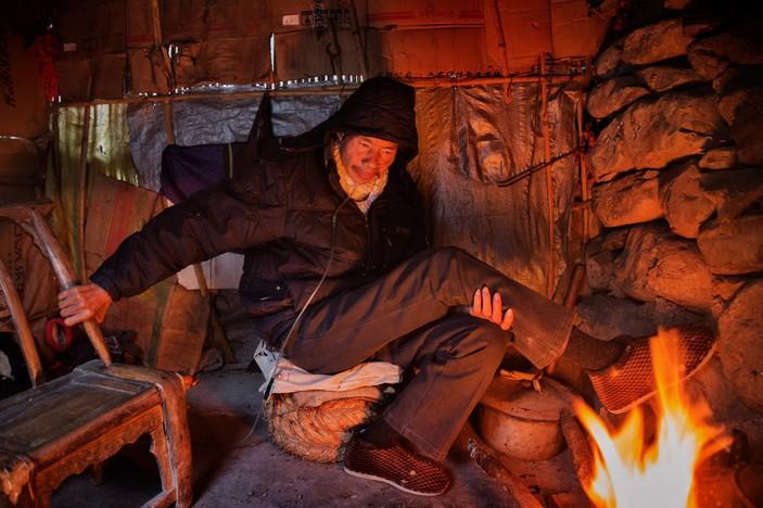 Хэ пытается согреться в сарае позади своего дома. Фото: Сим Чи Инь / VII