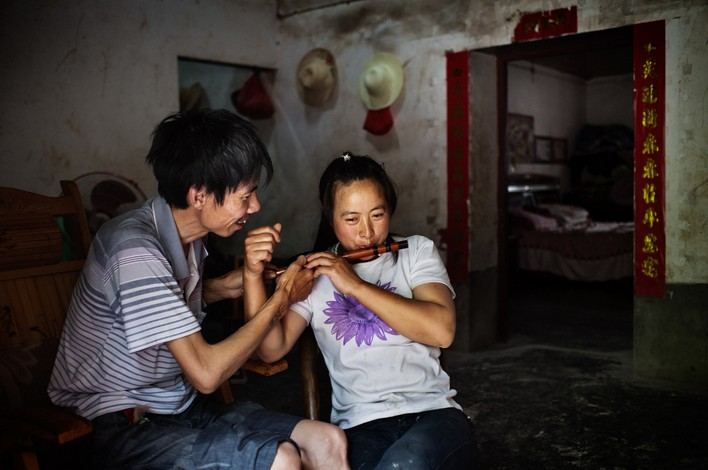 Фото: Спустя четыре месяца после операции на лёгких Хэ Цюаньгуй, бывший работник небольшой золотодобывающей шахты, и его жена Ми Шисю вернулись домой на лето. Фото Сим Чи Инь / VII