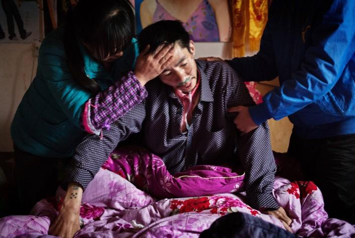 Изнемогающего Хэ поддерживают жена и сын, пока он пытается восстановить дыхание. Фото: Сим Чи Инь / VII