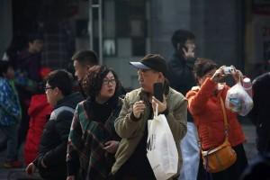 Мужчина держит смартфон в Пекине. Источник: Bloomberg News