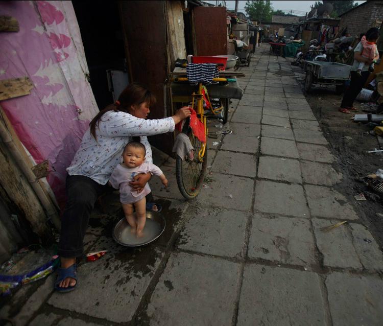 Мама купает малыша на улице