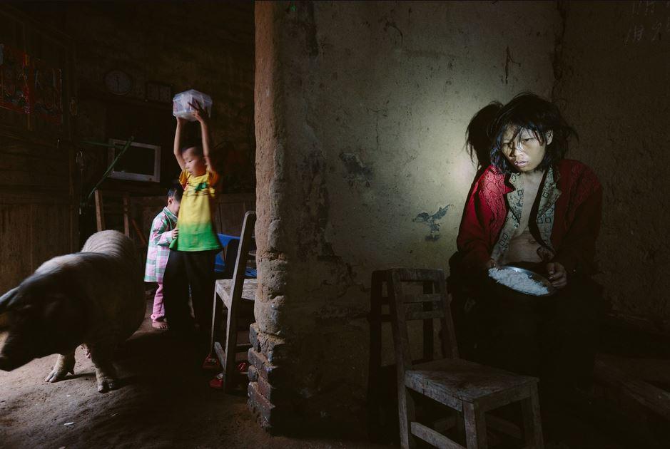9-летний Тун Сяо и его младшая сестра  Лин охраняют свою еду от свиньи. Их мать Ли (на фото справа) зарезала своего старшего сына ножом и заморила голодом остальных троих детей. Маоминг, Китай. Источник: lens.blogs.nytimes.com