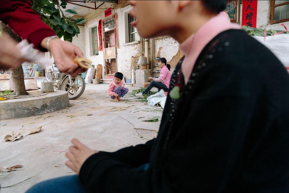 Сосед дает Юэи Оу перекусить. У него, у его сестры Юни Оу (она слева) и у их матери Сяо Линь расстройство психики, Чжаоцин, Китай. Источник: lens.blogs.nytimes.com