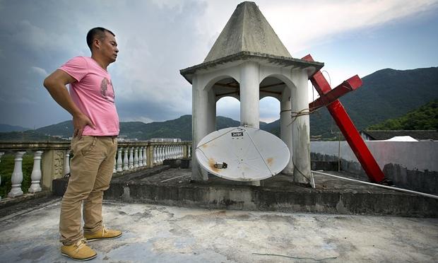 Лидер одной из церквей на крыше возле креста. Источник www.johnpiippo.com