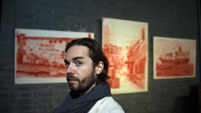 Александр Уэри на фоне картин Тао Хунцзина в галерее «Красные ворота». Фото: telegraph.co.uk