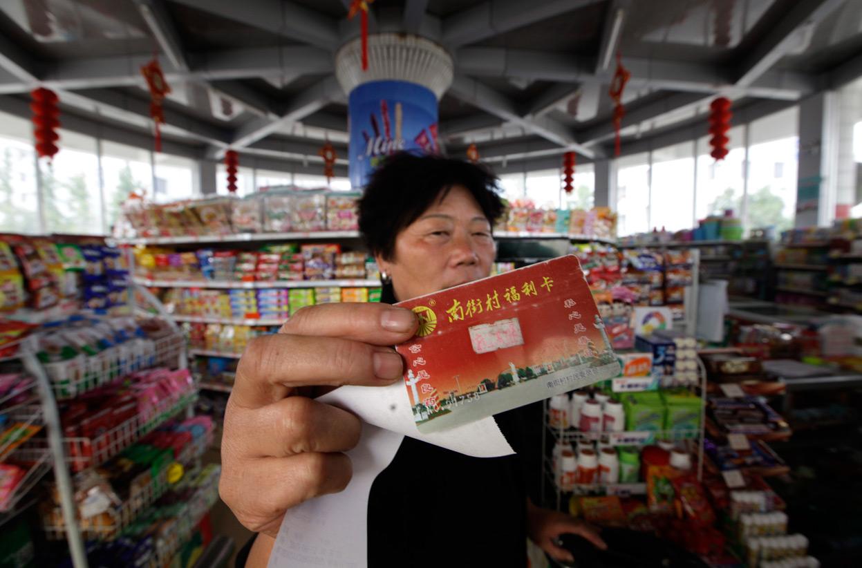 Жительница Наньцзе показывает свою социальную карточку, по которой она покупает воду в местном магазине. Фото: sf.co.ua