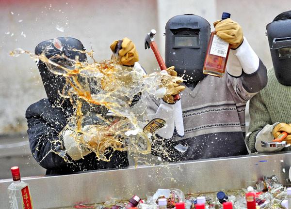 Китайцы уничтожают контрафактный алкоголь. Фото: chinadaily.com.cn