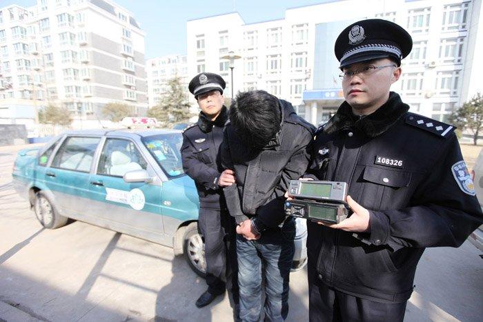 """Китайские полицейские делают """"атата"""" взломщику автомобилей. Фото: https://chinatravelgo.com/"""