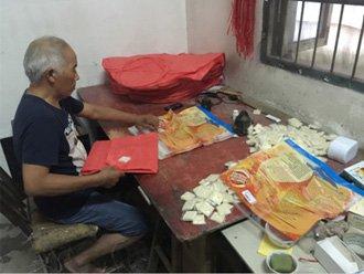 Житель китайской деревни изготавливает летающий фонарь в своем доме