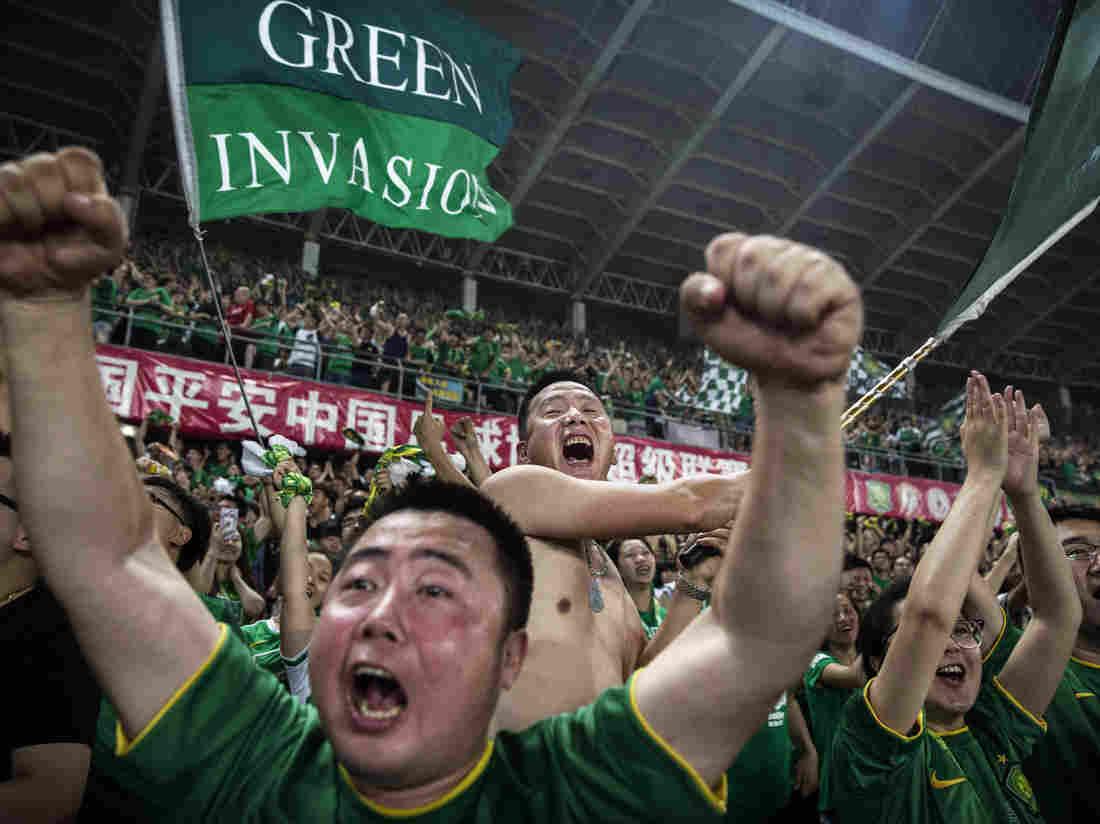 Болельщики клуба «Бэйцзи́н Гоань» из Пекина во время матча Суперлиги. Фото: Kevin Frayer/Getty Images