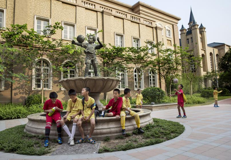 QINGYUAN, CHINA - JUNE 14: Young Chinese football players sit together in the campus as they wait to head to training at the Evergrande International Football School on June 14, 2014 near Qingyuan in Guangdong Province, China. The sprawling 167-acre campus is the brainchild of property tycoon Xu Jiayin, whose ambition is to train a generation of young athletes to establish China as a football powerhouse. The school is considered the largest football academy in the world with 2400 students, more than 50 pitches and a squad of Spanish coaches through a partnership with Real Madrid. (Photo by Kevin Frayer/Getty Images)