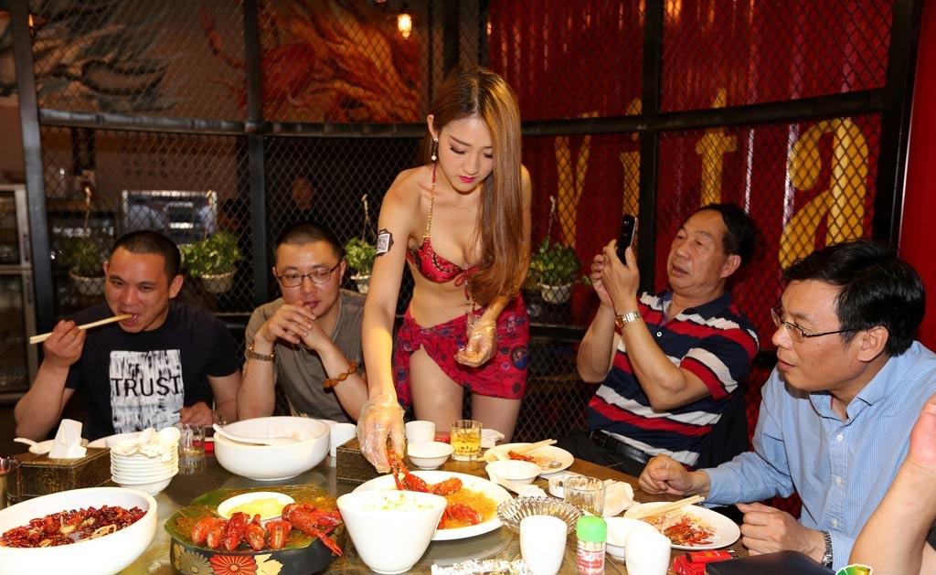 Официантка в бикини чистит креветки в ресторане в Шэньяне. Фото via Sina